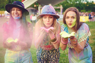 Three young women blowing coloured chalk powder at festivalの写真素材 [FYI03591184]