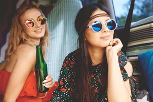 Two young boho women wearing sunglasses in recreational vanの写真素材 [FYI03591217]