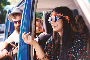 Young boho adults looking out and playing guitar in recreational van doorwayの写真素材 [FYI03591226]