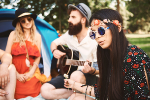 Young boho adults playing acoustic guitar at festivalの写真素材 [FYI03591232]