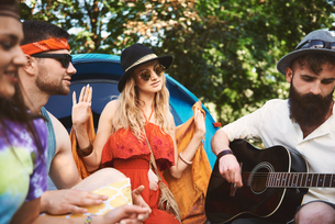 Young adult friends playing acoustic guitar while festival campingの写真素材 [FYI03591233]
