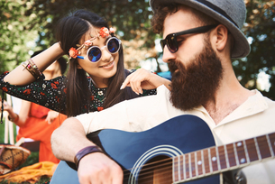 Young boho couple playing acoustic guitar at festivalの写真素材 [FYI03591235]