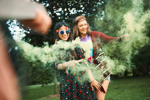 Young boho women dancing with green smoke flare  at festivalの写真素材 [FYI03591256]