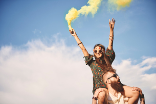Young boho woman holding yellow smoke flare on boyfriend's shoulders at festivalの写真素材 [FYI03591258]