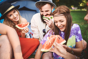 Young boho adult friends eating melon slices at festivalの写真素材 [FYI03591264]
