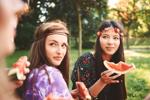 Young boho women eating melon slice at festivalの写真素材 [FYI03591266]