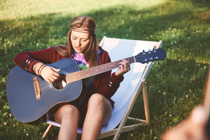 Young boho woman sitting on deckchair playing acoustic guitar at festivalの写真素材 [FYI03591267]
