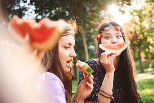 Young boho women making smiley face with melon slice at festivalの写真素材 [FYI03591269]