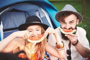 Young couple in trilbies making smiley face with melon slice at festivalの写真素材 [FYI03591270]
