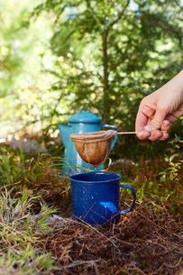 Woman making coffee in forest, close-up, Colgate Lake Wild Forest, Catskill Park, New York State, USの写真素材 [FYI03591357]