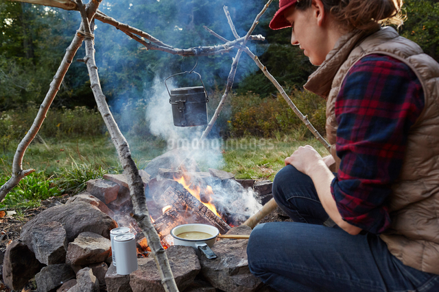 Woman sitting beside camp fire, cooking food, Colgate Lake Wild Forest, Catskill Park, New York Statの写真素材 [FYI03591358]