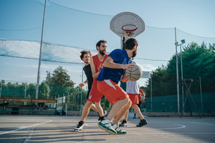 Friends on basketball court playing basketball gameの写真素材 [FYI03591383]
