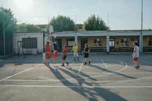 Friends on basketball court playing basketball gameの写真素材 [FYI03591390]