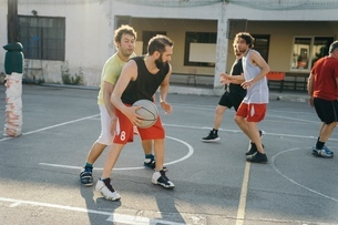 Friends on basketball court playing basketball gameの写真素材 [FYI03591395]