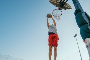 Man jumping for basketball hoopの写真素材 [FYI03591407]