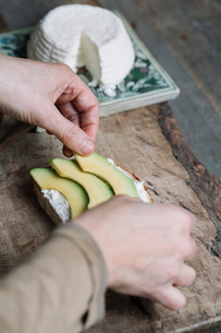 Woman placing slices of avocado onto sliced bread with ricotta, close-upの写真素材 [FYI03591447]