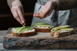 Woman sprinkling chopped walnuts onto avocado bruschetta, mid sectionの写真素材 [FYI03591451]