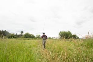 Fisherman with fishing rod on grass field, Clark Fork, Montana and Idaho, USの写真素材 [FYI03591477]