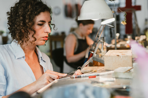 Female jeweller shaping silver metal at workbenchの写真素材 [FYI03591506]