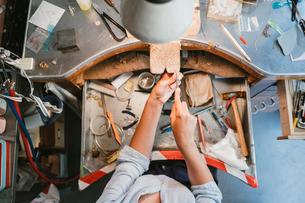 Overhead view of female jeweller's hands working at workbenchの写真素材 [FYI03591509]