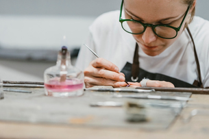 Female jeweller working with miniature hand tool at workbenchの写真素材 [FYI03591539]