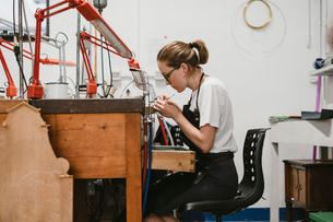 Female jeweller working with miniature hand tool at workbenchの写真素材 [FYI03591541]