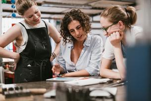 Three female jewellers looking at digital tablet at workbench meetingの写真素材 [FYI03591560]