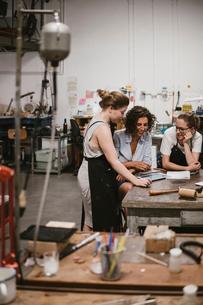 Three female jewellers looking at digital tablet at workbench meetingの写真素材 [FYI03591561]