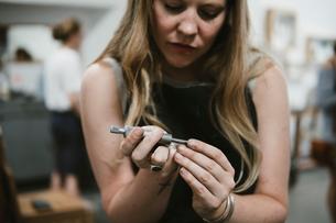Female jeweller using hand tool in jewellery workshopの写真素材 [FYI03591565]