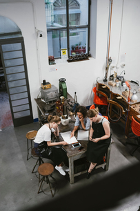 High angle view of three female jewellers looking at sketchpad at workbench meetingの写真素材 [FYI03591573]