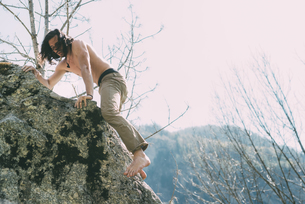 Bare chested and bare foot male boulderer climbing boulder, Lombardy, Italyの写真素材 [FYI03591772]