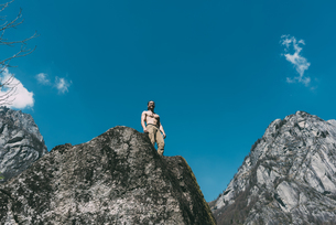 Low angle view of bare chested young male boulderer looking down boulder top, Lombardy, Italyの写真素材 [FYI03591777]