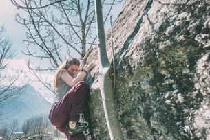 Young female boulderer climbing boulder, Lombardy, Italyの写真素材 [FYI03591797]