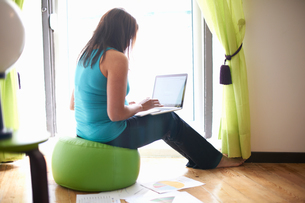 Woman using laptop at homeの写真素材 [FYI03592032]