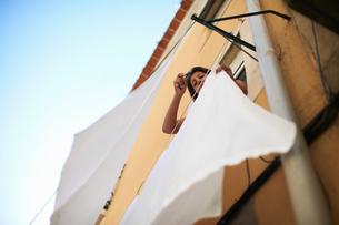 Woman hanging sheet on laundry lineの写真素材 [FYI03592033]