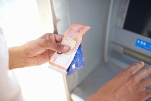 Woman using cash dispenserの写真素材 [FYI03592037]
