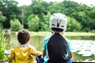 Two young brothers sitting at water's edge, older brother wearing cycling helmet, rear viewの写真素材 [FYI03592183]