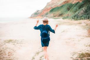 Mid adult woman dancing along beach, rear viewの写真素材 [FYI03592219]