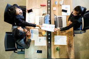 Three businesswomen sitting at desk, using laptops, holding smartphone, passing document, overhead vの写真素材 [FYI03592340]