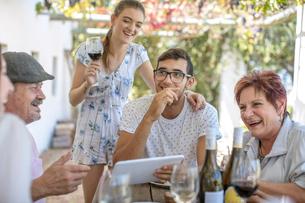 Family having lunch outdoors under grapevine trellisの写真素材 [FYI03592380]