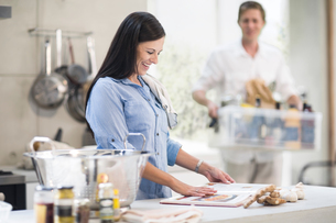 Husband and wife making preparations in kitchenの写真素材 [FYI03592414]