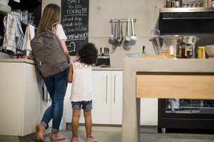 Sisters looking up at blackboard in kitchenの写真素材 [FYI03592436]