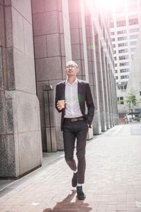 Cool businessman with takeaway coffee strolling along sidewalk, New York, USAの写真素材 [FYI03592488]
