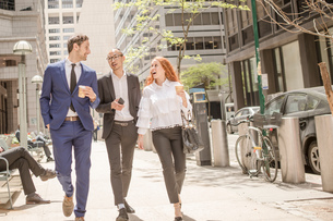 Young businesswoman and businessmen with takeaway coffee strolling along sidewalk, New York, USAの写真素材 [FYI03592489]