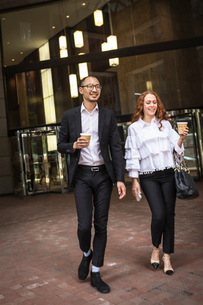 Young businesswoman and man with takeaway coffee strolling on sidewalk, New York, USAの写真素材 [FYI03592490]