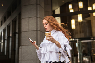 Young businesswoman with takeaway coffee looking at smartphone on sidewalk, New York, USAの写真素材 [FYI03592491]