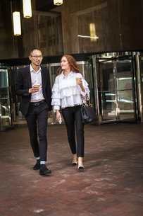 Young businesswoman and man with takeaway coffee strolling on sidewalk, New York, USAの写真素材 [FYI03592492]