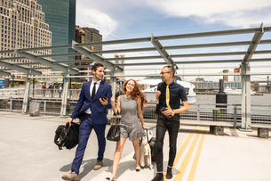 Businessmen and woman with luggage walking and talking on waterfront, New York, USAの写真素材 [FYI03592525]