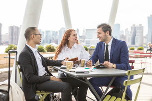 Businessmen and woman meeting at waterfront cafe with New York skyline, USAの写真素材 [FYI03592527]