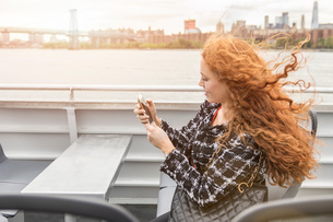 Young businesswoman on passenger ferry deck looking at smartphoneの写真素材 [FYI03592550]